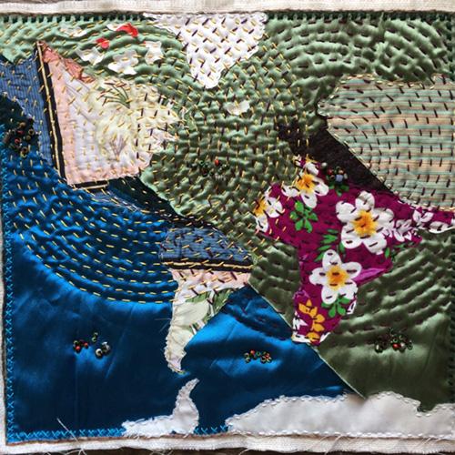 Narrativa artes textiles. Arpillera La Broma. Primer plano de la imagen. Mapa realizado con trozos de telas estampadas y bordada con hilos de colores en forma de en círculos concéntricos